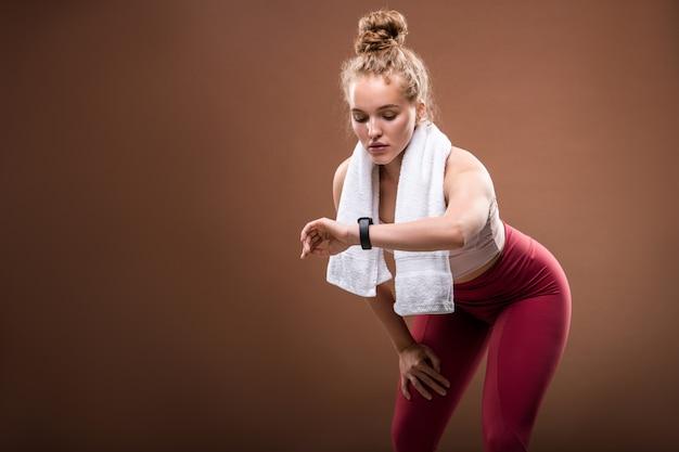 Stanca giovane sportiva bionda in abbigliamento sportivo che guarda fitbit al polso mentre fa un difficile esercizio fisico su marrone