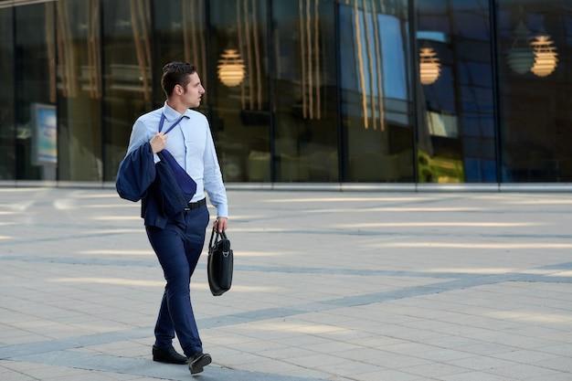Stanco giovane uomo d'affari con custodia che va dopo il lavoro quando fa caldo