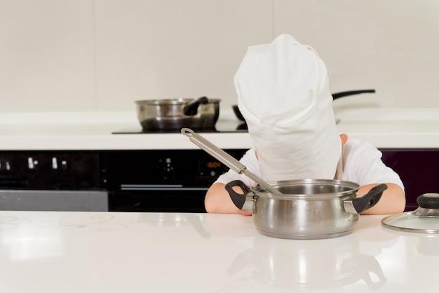 Stanco giovane chef che riposa posando la testa sul tavolo della cucina