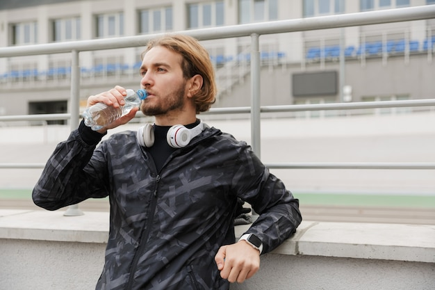 Stanco giovane sportivo in forma che riposa dopo l'allenamento allo stadio, bevendo acqua da una bottiglia