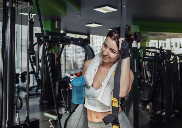 Stanco giovane donna adatta in possesso di una bottiglia di acqua in palestra