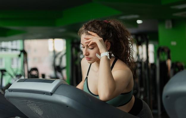 Stanco giovane donna adatta in abiti sportivi sul tapis roulant in palestra. il concetto di uno stile di vita sano, riscaldamento, fitness.