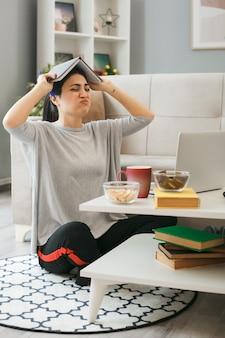La ragazza stanca ha coperto la testa con il libro che si siede sul pavimento dietro il tavolino da caffè nel soggiorno