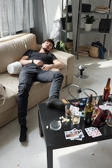 Giovane stanco in jeans neri che dorme sul divano con la gamba sul tavolino da caffè con birra e fiches da poker dopo una festa esilarante