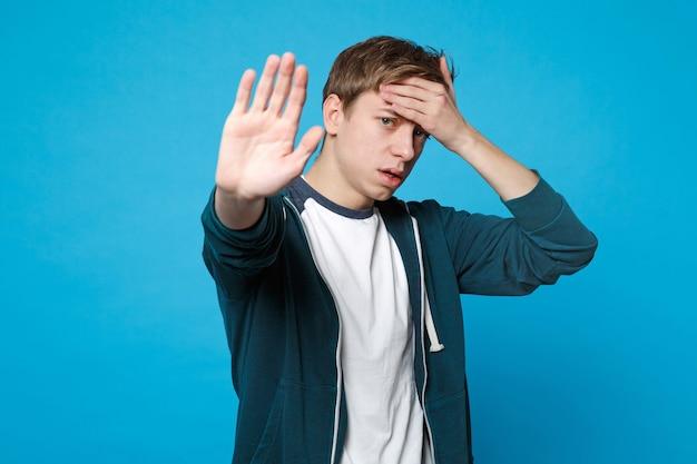Giovane stanco in abiti casual che mette la mano sulla fronte, mostrando il gesto di arresto con il palmo isolato sulla parete blu.