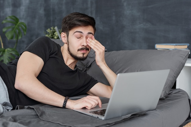Giovane stanco che ha affaticamento degli occhi sdraiato sul letto con il computer portatile e lo sfregamento degli occhi