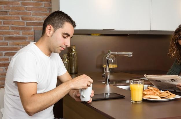 Giovane stanco che tiene una tazza di caffè a casa colazione mentre sua moglie legge le notizie sul giornale