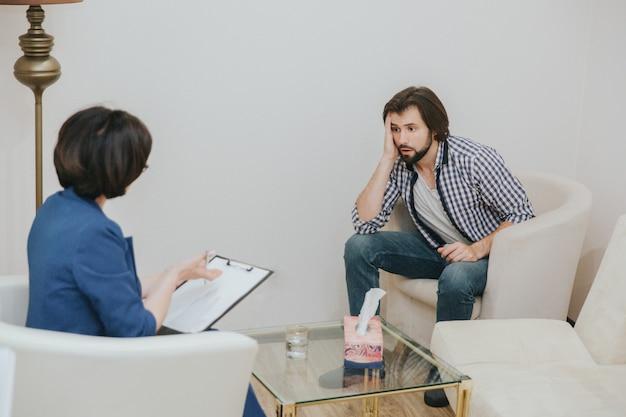 Il giovane stanco è seduto davanti al medico e la sta guardando. lui è annoiato. guy tiene la mano vicino alla testa. la terapista sta guardando i suoi documenti.