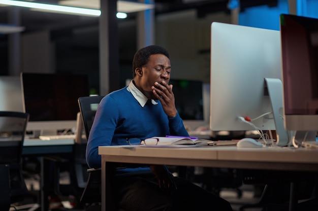 Il giovane stanco lavora nell'ufficio notturno