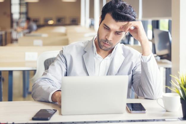 Gli occhi stanchi di un giovane sono stanchi per il lavoro al computer