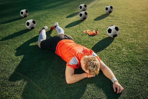 Giovane giocatore stanco sdraiato sul prato con la faccia rivolta a terra