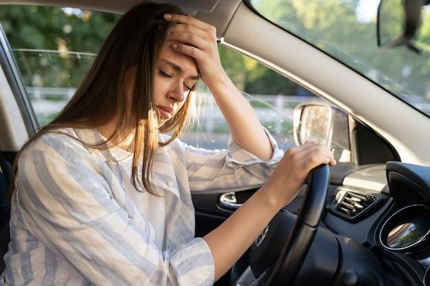 L'automobilista stanco di una giovane donna soffre di mal di testa o dolore all'emicrania all'interno del veicolo tocca la fronte
