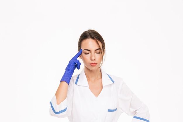 Stanco giovane donna medico indossando guanti di gomma e uniformi in piedi isolato sopra il muro bianco