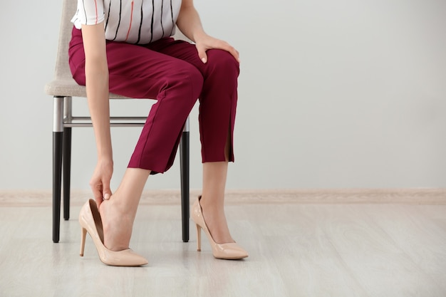 Giovane donna stanca che sente dolore alle gambe all'interno