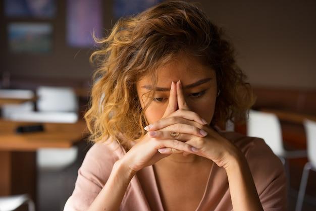 Testa pendente della giovane donna stanca sulle mani