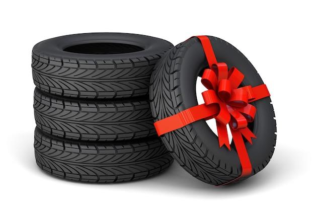 Pneumatici in regalo set di quattro pneumatici uno legato con un nastro regalo rosso con un fiocco isolato su bianco