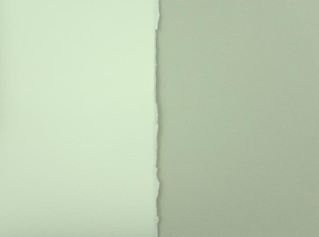 Carta bianco titanio con unico strappo del lato su carta grigio chiaro