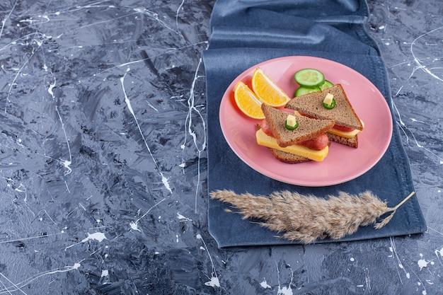 Pane tostato con formaggio e verdure a fette sul piatto rosa.