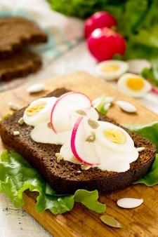 Toast sandwich con uovo, ravanello, semi di zucca e panna acida, fuoco selettivo.