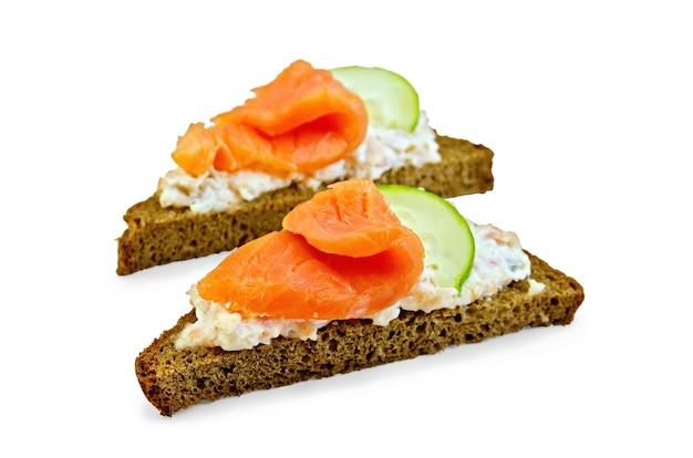 Tostare due fette di pane di segale con panna, salmone e cetriolo isolati su sfondo bianco