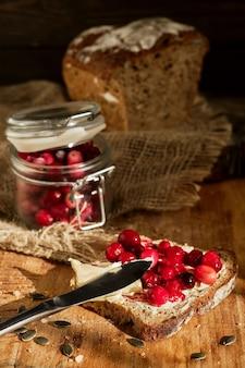 Toast con mirtilli rossi e burro su pane a lievitazione naturale fatto in casa, luce solare sul tavolo