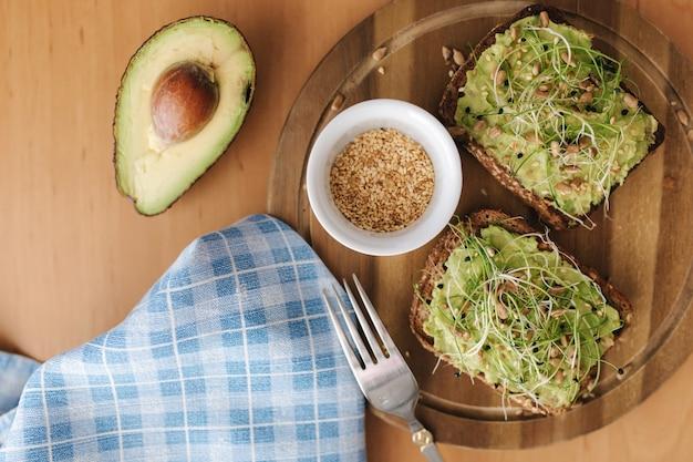 Toast con microgreens e guacamole sopra. pane tostato di segale su tavola di legno. cibo sano a casa. concetto di cibo vegano. vista dall'alto