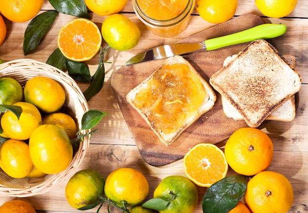 Pane tostato con marmellata di arance e mandarini con frutta fresca sulla tavola di legno, vista dall'alto