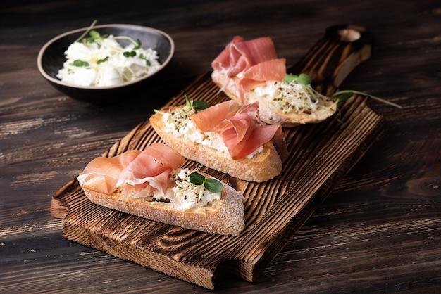 Toast con ricotta di prosciutto e microgreens, crostini di prosciutto su fondo di legno scuro, stile rustico.