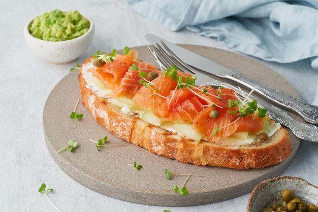 Toast con salmone, crema di formaggio e fette di cetriolo sul tavolo di cemento bianco