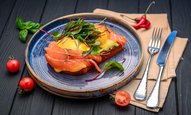 Toast con salmone, uovo in camicia e avocado su un piatto. prima colazione al ristorante