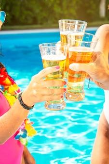 Brindisi con tre bicchieri di birra in piscina