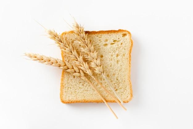 Pane tostato tagliato a fette e spighe di grano su uno sfondo bianco. vista dall'alto, piatto.