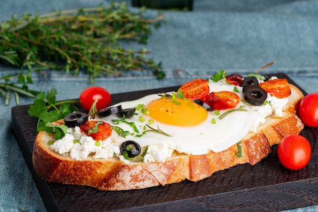 Toast di pane tostato con uova fritte con tuorlo giallo e pomodori, olive, cosparsi di erbe sul tagliere di legno scuro sul tovagliolo denim blu, vista laterale