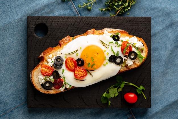 Toast di pane tostato con uova fritte con tuorlo giallo e pomodori, olive, cosparsi di erbe sul tagliere di legno scuro sul tovagliolo di jeans blu, vista dall'alto