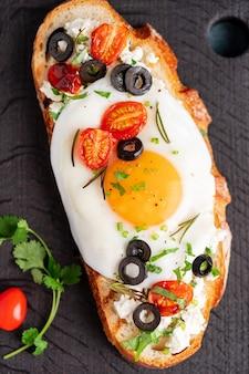 Toast di pane tostato con uova fritte con tuorlo giallo e pomodori, olive, cosparsi di erbe su tavola di legno scuro sul tovagliolo denim blu, verticale, vista dall'alto, primo piano