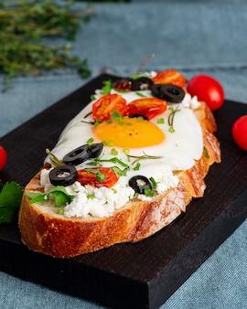 Toast di pane tostato con uova fritte con tuorlo giallo e pomodori, verticale, vista laterale