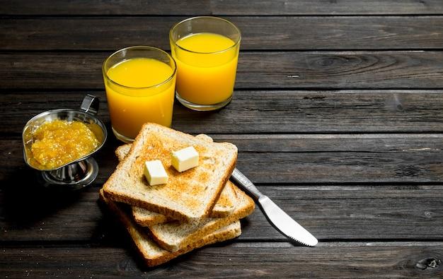 Pane tostato con burro, marmellata di arance e succo.
