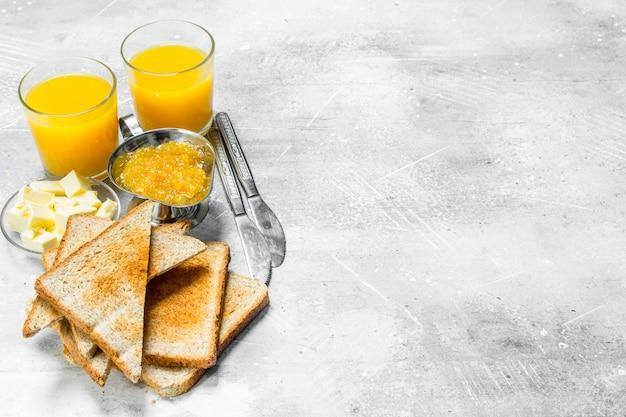Pane tostato con burro e marmellata di arance. su un tavolo rustico.