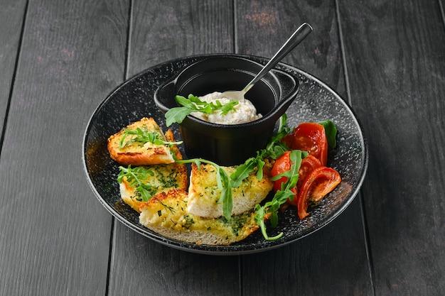 Pane tostato all'aglio, pomodoro e paté di pollo su un piatto