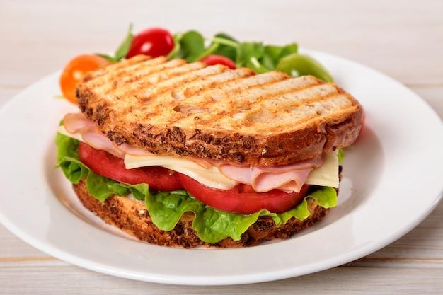 Panino del formaggio e del prosciutto tostato sulla tavola di legno