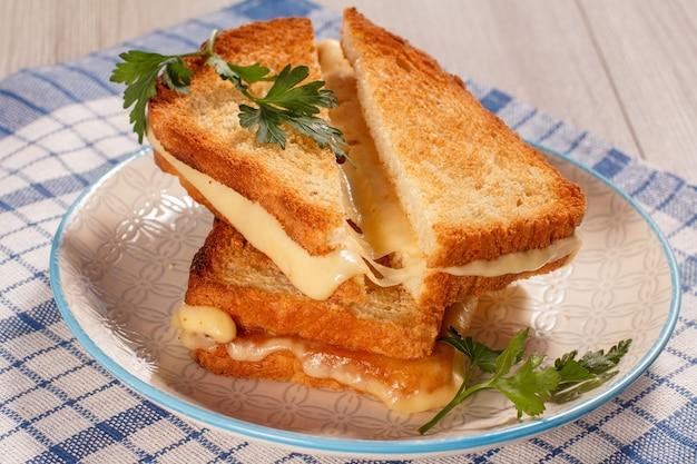 Fette di pane tostate con formaggio e prezzemolo verde su piatto bianco con tovagliolo da cucina blu. buon cibo a colazione