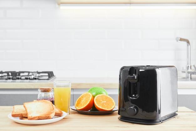 Tostapane con piatti e toast con succo di frutta fresco su un tavolo da cucina in legno