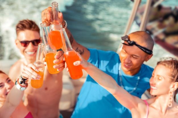 Brindando all'amicizia. vista dall'alto di giovani allegri che bevono bevande analcoliche su uno yacht mentre propongono brindisi alla loro amicizia
