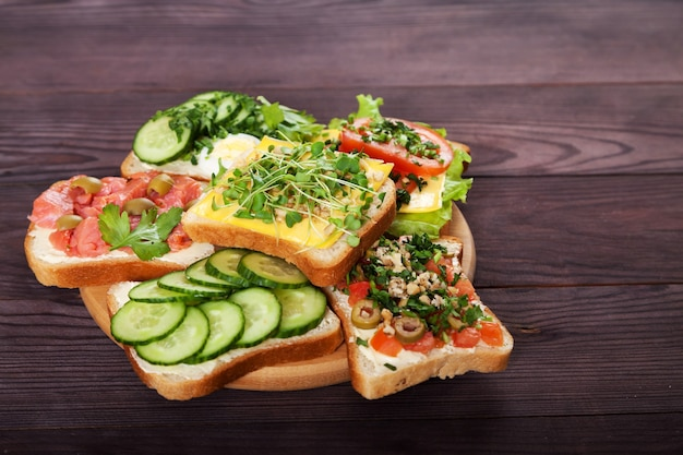 Toast, panini con crema di formaggio, cetrioli, pomodori, salmone, germogli, uova su un legno marrone.
