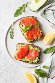 Toast con avocado e salmone sul piatto su sfondo bianco