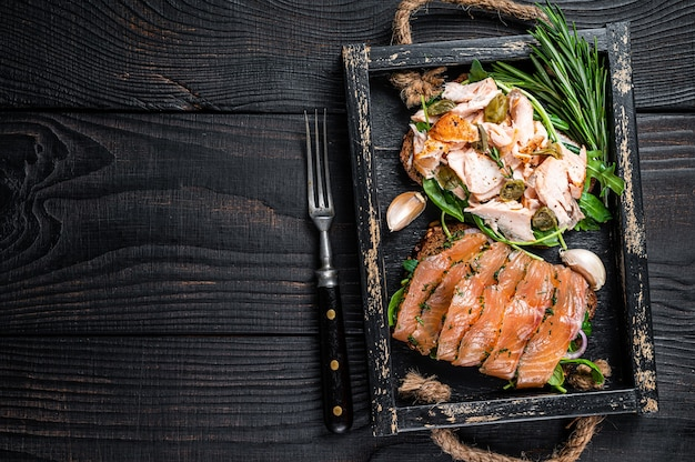 Toast con salmone affumicato caldo e freddo, rucola in vassoio di legno con erbe aromatiche. fondo in legno nero. vista dall'alto. copia spazio.