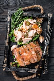 Toast con salmone affumicato caldo e freddo, rucola in vassoio di legno con erbe aromatiche. fondo in legno nero. vista dall'alto.