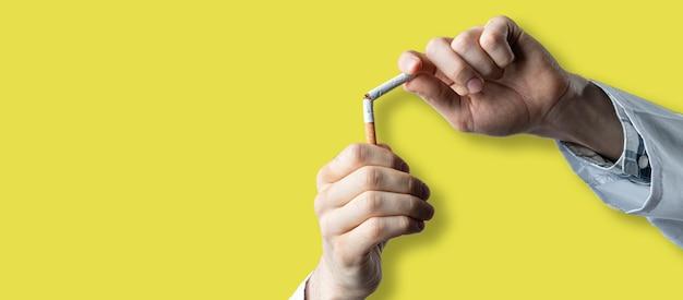 Il concetto di dipendenza da tabacco, smettere e smettere di fumare nicotina, frenare a mano una sigaretta isolata