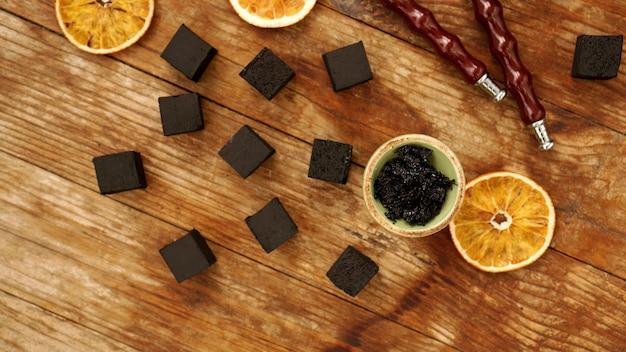 Tabacco nella ciotola per narghilè sul tavolo di legno con carbone e fette d'arancia essiccate