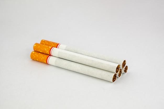 Mucchio di sigarette di tabacco su sfondo bianco
